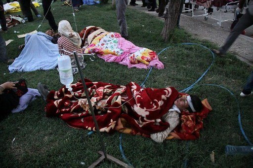 Injured Iranians lie on the grass outside a hospital in the town of Ahar, some 60 kms east of Tabriz, after a strong earthquake hit northwestern Iran on August 11, 2012.