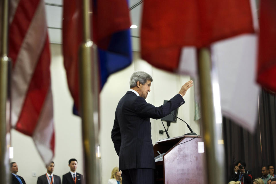 Seen through the flags of participating countries, U.S. Secretary of State John Kerry speaks to the media during a new conference at ASEAN in Bandar Seri Begawan, Brunei on Monday, July 1, 2013. (AP Photo/Jacquelyn Martin, Pool)