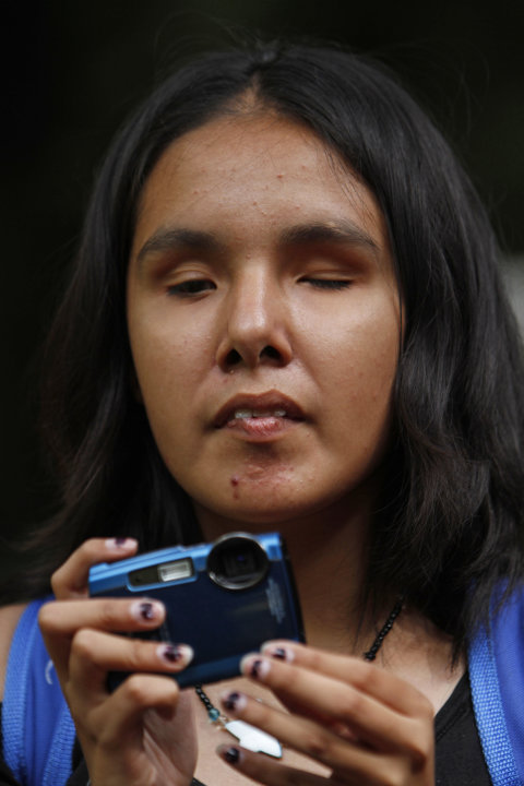 In this photo taken Sept. 7, 2011, Nancy Sarahi feels her camera as she prepares to take a photograph at a park in Mexico City. Sarahi is one of 30 visually impaired or blind people learning photograp