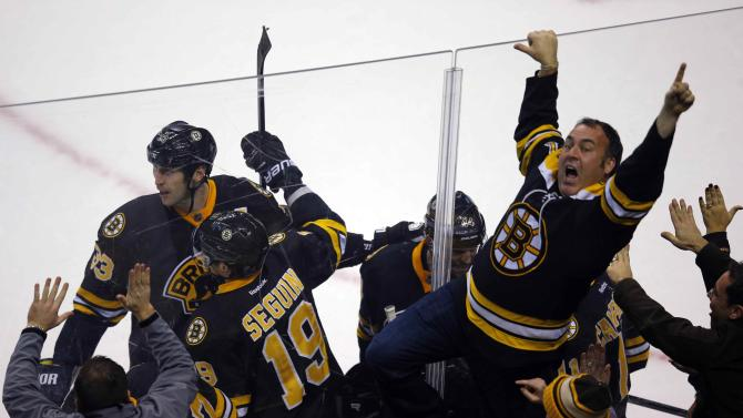 Boston Bruins and their fans celebrate after scoring a goal against the New York Rangers during their NHL hockey game in Boston