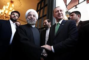 Iranian President Hassan Rouhani (L) shakes hands with…