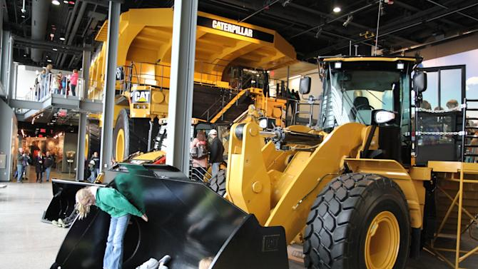 This December 2012 photo shows equipment on display at the Caterpillar Visitors Center in Peoria, Ill. Caterpillar Inc. manufactures heavy equipment that bulldozes, digs, lifts and performs other tasks at construction and mining sites. The center lets visitors climb inside the machines for a closer look while computer simulations provide an opportunity to learn how to manipulate the controls. (AP Photo/Fritz Faerber)