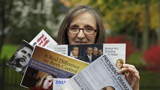 "In this photo taken Oct. 19, 2012,  Jean Gianfagna displays some of the political mailers her family receives at her home in Westlake, Ohio. Gianfagna says her family is ""deluged"" and sometimes gets four of the same piece at a time _ her husband and two grown kids all get their own. (AP Photo/Mark Duncan)"