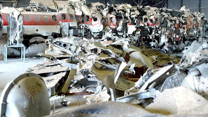 FILE - In this Monday Dec. 15, 2003 file photo, a view of the pieces of the reconstructed wreckage, in background, of the Itavia DC-9 passenger jetliner which crashed near the tiny Mediterranean island of Ustica June 27, 1980, in a hangar in Pratica di Mare, near Rome. An Italian court has ordered the government to pay euro100 million in civil damages to relatives of 81 people killed in a mysterious 1980 airplane disaster. The Government said Tuesday, Sept. 13, 2011, it would appeal the decision of the Palermo tribunal, which on Monday held Italy's transport and defense ministries liable for having failed to guarantee the security of the flight. The Itavia DC-9 airliner crashed en route from Bologna to Palermo near the tiny Mediterranean island of Ustica. The cause remains a mystery: some blame a bomb, others say the aircraft might have been caught in the crossfire of a military aerial dogfight. Italy's high court in 2007 upheld the acquittals of two air force generals accused of withholding information about the crash. (AP Photo/Emiliano Grillotti, File)