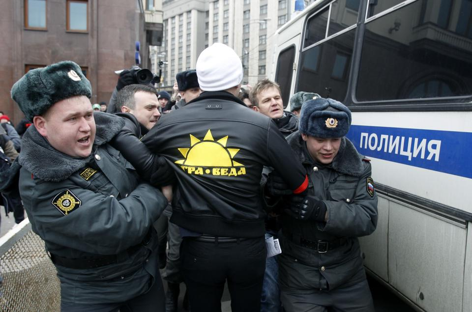 Police officers detain Russian opposition members outside the parliament building, background, in downtown Moscow, Wednesday, April 11, 2012. Russia's Prime Minister Vladimir Putin is to speak at Parliament on Wednesday in his first major public speech since his victory in the March 4 presidential election. (AP Photo/Misha Japaridze)