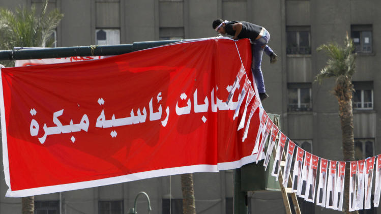 """An Egyptian protester hangs an Arabic banner reading, """"early presidential elections"""", during a protest in Tahrir Square, the focal point of Egyptian uprising, in Cairo, Egypt, Friday, May 17, 2013. Hundreds of protesters gathered to demand early presidential elections and the removal of the Muslim Brotherhood's regime. (AP Photo/Amr Nabil)"""