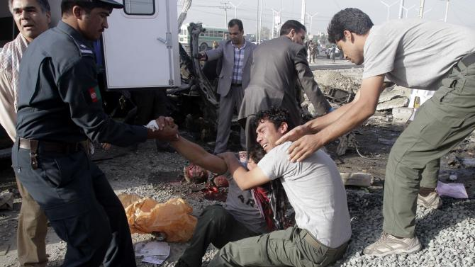 EDS NOTE: GRAPHIC CONTENT - Brothers of an Afghan mini-bus driver who was killed in a suicide bombing cry at the scene, Tuesday, Sept. 18, 2012 in Kabul, Afghanistan. A suicide bomber rammed a car packed with explosives into the mini-bus carrying foreign aviation workers to the airport in the Afghan capital early Tuesday, killing at least nine people in an attack a militant group said was revenge for an anti-Islam film that ridicules the Prophet Muhammad. (AP Photo/Ahmad Jamshid)