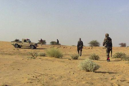 Fighters from the Tuareg separatist rebel group MNLA walk in the desert near Tabankort