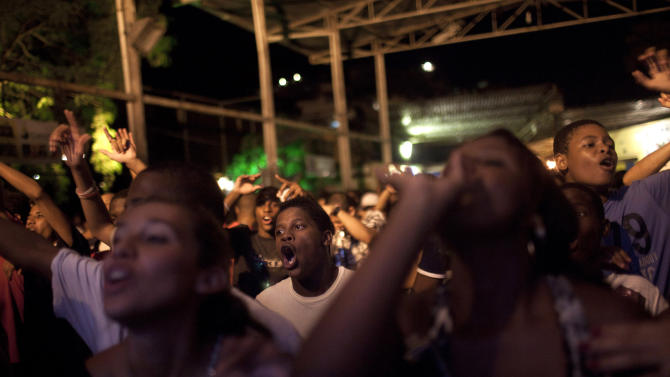 "In this Feb. 5, 2012 photo, people sing along during a funk ""baile"" in the Tabajaras slum in Rio de Janeiro, Brazil. In the last five years, the genre has expanded its reach and enjoyed more social acceptance, with the help of an association of funk artists and supporters, Apafunk, and the backing of liberal legislators.  (AP Photo/Felipe Dana)"