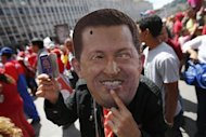 A supporter of Venezuela's President Hugo Chavez wears a mask depicting him during a rally in Caracas February 27, 2013. REUTERS/Jorgre Silva