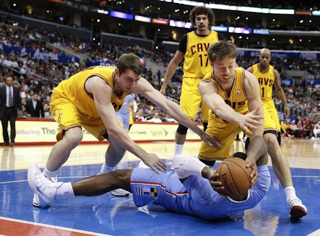 Los Angeles Clippers's Glen Davis, bottom, fights for the ball with Cleveland Cavaliers's Tyler Zeller, left, and Matthew Dellavedova during the first half of an NBA basketball game on Sunday,