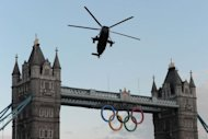 A Sea King helicopter carrying the Olympic Flame flies over London&#39;s Tower Bridge