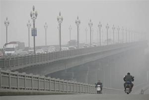 People ride along a bridge on a smoggy day in Nanjing
