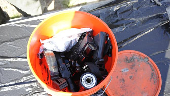 This undated photo provided by the FBI shows a Home Depot bucket containing gun parts, ammunition and other items discovered at a Parishville, N.Y. reservoir after a man jailed in Alaska admitted to a series of killings, including an Anchorage barista and a couple from Vermont. (AP Photo/FBI)
