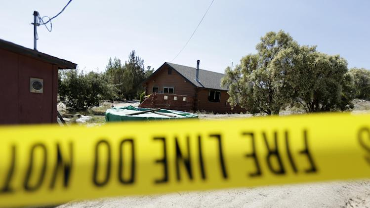 Police tape lines the perimeter of a partially burned home Tuesday, Aug. 6, 2013, near the U.S.-Mexico border in Boulevard, Calif. The husband of a woman whose body was found in the house said Tuesday that he knew the man suspected of killing his wife and abducting one or both of their children. (AP Photo/Gregory Bull)