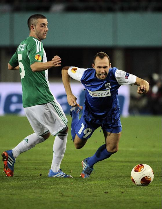 Rapid's MThanos Petsos, left, and Genk's Thomas Buffel challenge for the ball during their Europa League  group G soccer match between SK Rapid Vienna and KRC Genk, in Vienna, Austria, Thursday, Nov.