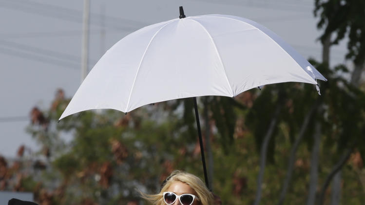 Paris Hilton arrives to unveil the Paris Beach Club, which she designed in collaboration with Philippine developer Century Properties, Thursday, March 13, 2014, in Paranaque city, southeast of Manila, Philippines. The bean-shaped, three-story club fronting a man-made beach is within the resort-themed Azure condominium community. Hilton unveiled her first real estate project Thursday in metropolitan Manila and said she wants to follow in the footsteps of her great-grandfather and grandfather, who led a luxury hotel empire. (AP Photo/Bullit Marquez)