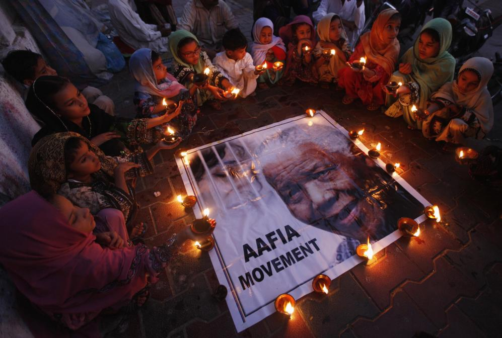 Children hold earthen lamps in tribute to former South African President Mandela, organized by Aafia Movement in Karachi