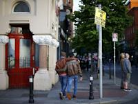 Men walk past a no vote campaign poster in central Dublin as Ireland holds a referendum on gay marriage