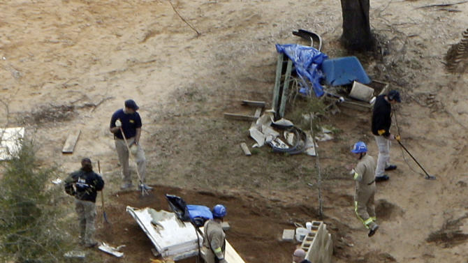 """FILE -- In this photo taken Feb. 8, 2013, authorities continue their investigation at the site in Midland City, Ala., where a five year old boy was held hostage in an underground bunker. Dale County Sheriff Wally Olson on Thursday, March 7, 2013 said officers stormed the bunker because the man had told them something """"real, real bad"""" was going to happen if they didn't meet his demands. (AP Photo/Dave Martin, File)"""