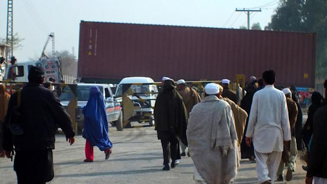 Pakistani tribal residents walk past a NATO truck as it reportedly brings supplies from neighboring Afghanistan in Jamrud, in the tribal area of Khyber, Pakistan, on Monday, Feb. 11, 2013.  The U.S. says it has started using the land route through Pakistan to pull American military equipment out of Afghanistan. (AP Photo/Jibran Yousufzai)