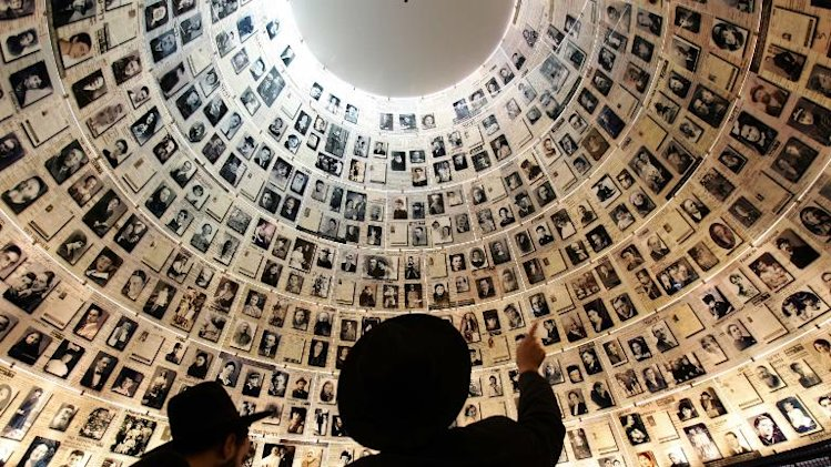 Ultra-Orthodox Jews look at the hundreds of photo portraits of people killed during the Nazi holocaust in the Hall of Names inside the Yad Vashem Holocaust Museum in Jerusalem, on November 1, 2005