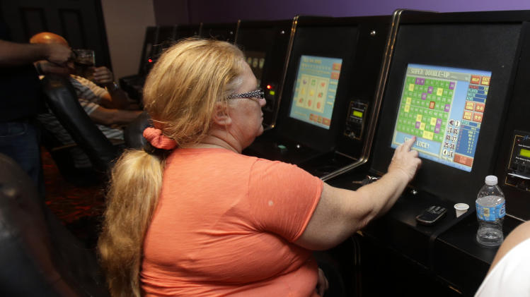 "Gladys Fundora plays a sweepstake game   at the New York NewYork Arcade in Hialeah, Fla., Thursday, April 10, 2013. Gaming centers also known as ""Internet cafes"" are now illegal in Florida. Gov. Rick Scott signed a bill Wednesday that bans up to 1,000 storefront operations across the state. The new law took effect immediately after Scott signed the bill.(AP Photo/Alan Diaz)"