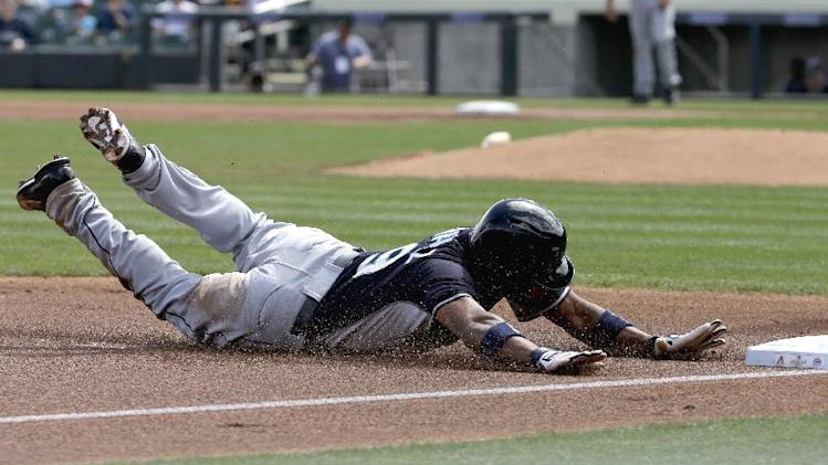 Seattle Mariners' Endy Chavez steals third base on a over throw against the Arizona Diamondbacks during the first inning of a spring exhibition baseball game, Thursday, March 13, 2014, in Scottsdale, Ariz