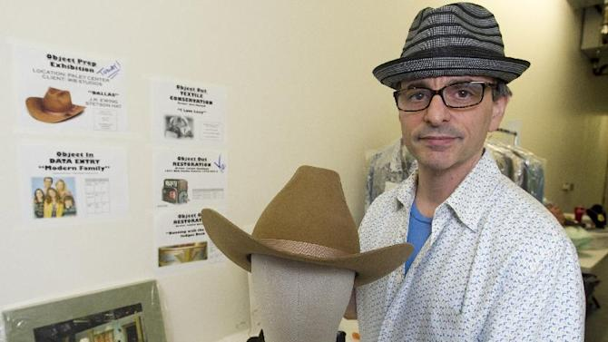 """In this Friday, Nov. 30, 2012 photo, James Comisar shows a Stetson hat worn by actor Larry Hagman portraying oil tycoon J. R. Ewing in the """"Dallas"""" television show. The item is part of his television memorabilia collection in a temperature- and humidity-controlled warehouse in Los Angeles. (AP Photo/Damian Dovarganes)"""
