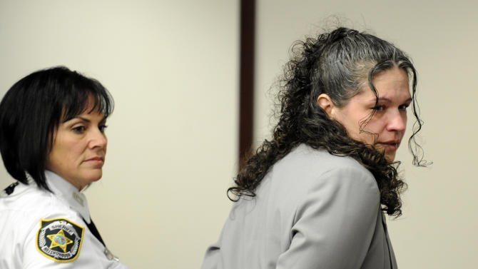 "Dee Dee Moore is led into a Hillsborough County courtroom for the reading of the verdict in her murder trial Monday, Dec. 10, 2012 in Tampa, Fla. Moore was convicted Monday of first-degree murder in the slaying of a lottery winner in central Florida and sentenced to mandatory life without parole by a judge who called her ""cold, calculating and cruel."" (AP Photo/The Tampa Tribune, Chris Urso, Pool)"