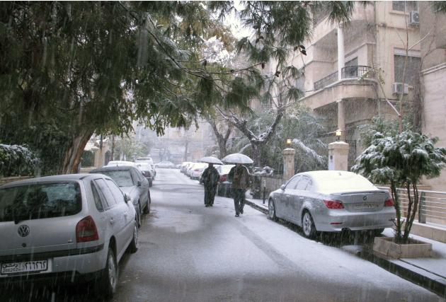 People walk on a street during snow fall in Damascus