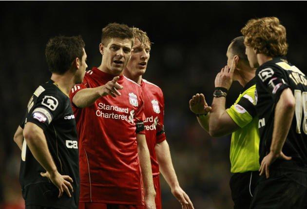 Liverpool's Steven Gerrard, second left, talks with referee Neil Swarbrick after an incident involving Oldham Athletic's Tom Adeyemi, not pictured, and a member of the crowd during their FA Cup third