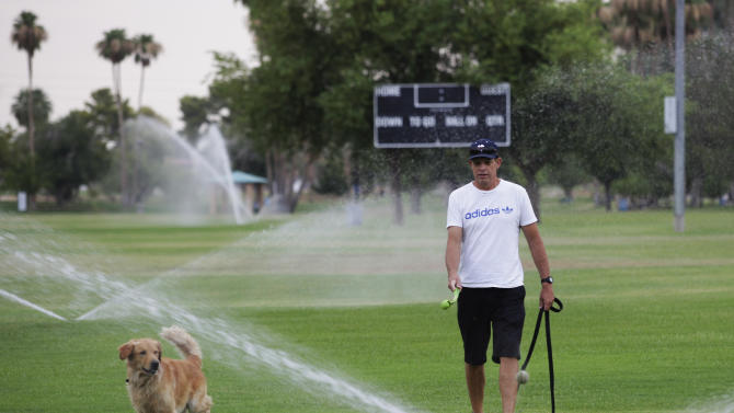Chris Jolley, right, of Scottsdale, runs his dog Logan through sprinklers at a local park on Saturday, June 29, 2013, in Scottsdale. Excessive heat warnings will continue for much of the Desert Southwest as building high pressure triggers major warming in eastern California, Nevada, and Arizona. Temperature's are expected to get as high as 118 degrees. (AP Photo/Rick Scuteri)