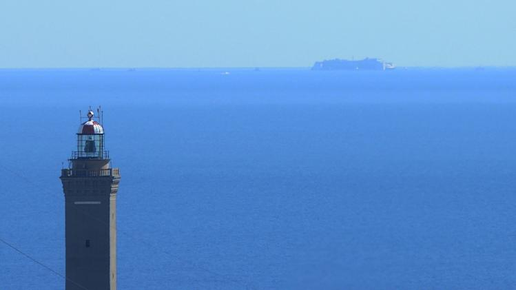 The wreck of the Costa Concordia cruise ship can be barely seen near the horizon line with in foreground one of the best known landmarks of Genoa, the Lanterna, a lighthose built in 1543, Saturday, July 26, 2014. After more than two years since it slammed into a reef along the coastline of Isola del Giglio the wreck is scheduled to conclude its last journey tomorrow in the Italian port of Genoa, where it will be scrapped. (AP Photo/Fabio Palli, Lapresse) ITALY OUT