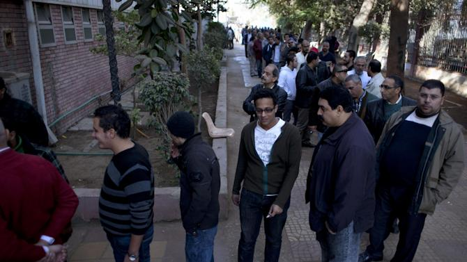 Egyptians queue to vote outside a gymnasium hall that is used as a polling station during the second round of a referendum on a disputed constitution drafted by Islamist supporters of president Mohammed Morsi, in Giza, Egypt, Saturday, Dec. 22, 2012. (AP Photo/Nasser Nasser)