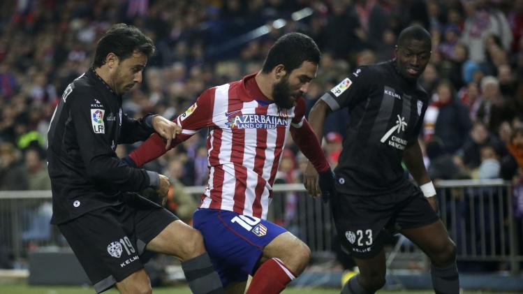 Atletico Madrid's Arda controls the ball between Levante's Lopez and Diop during their Spanish first division soccer match at Vicente Calderon stadium in Madrid