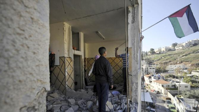File - In this Nov. 19, 2014 file photo Palestinians hang national flag inside the demolished apartment of Abdel Rahman al-Shaludi in east Jerusalem on. Israeli authorities demolished the apartment as a punitive measure after al-Shaludi's deadly attack with his car on a Jerusalem train station last month which left two people dead.  Israel says it is resuming demolitions because it needs more tools to stop a recent wave of Palestinian attacks on Jews.  (AP Photo/Mahmoud Illean, File)