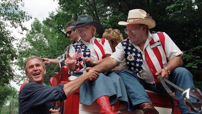 """FILE - In this July 4, 1999 file photo, presidential hopeful George W. Bush greets supporters at the start of a parade in Merrimack, N.H. In 2000, likely Republican presidential candidate Scott Walker, who was then a 32-year-old state Assembly member during Bush's first presidential bid, wrote an open memo he titled """"Campaign Strategy"""" in which he offered detailed advice on how he thought the then-Texas governor should be crafting his message to win the presidency, including what type of television ads he should run.  (AP Photo/Joel Page, File)"""