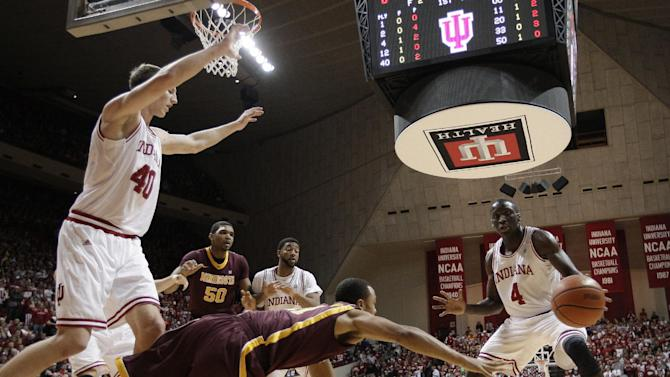 Minnesota's Joe Coleman makes a pass while being defended by Indiana's Cody Zeller, left, and Victor Oladipo (4) during the first half of an NCAA college basketball game Thursday, Jan. 12, 2012, in Bloomington, Ind. (AP Photo/Darron Cummings)