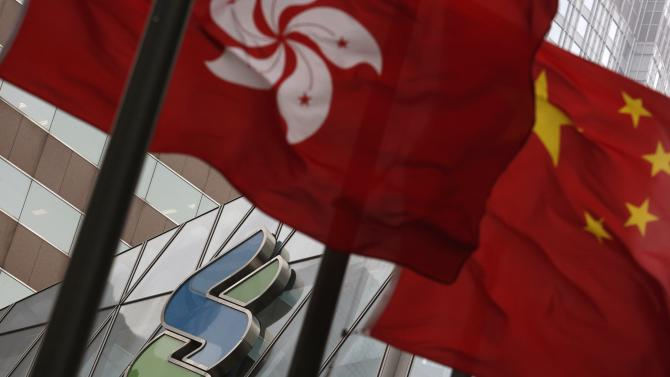 The logo of Standard Chartered bank is seen behind a Hong Kong flag and a Chinese national flag in Hong Kong
