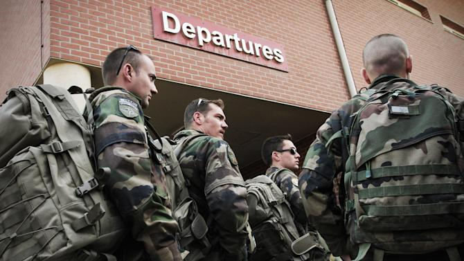 French soldiers, part of the NATO- led International Security Assistance Force (ISAF) wait to be checked outside the terminal before their departure in Kabul, Afghanistan, Wednesday, March 28, 2012. 200 French troops left Afghanistan on Wednesday, the group of soldiers are part of 1000 French troops set to leave the country this year. (AP Photo/Musadeq Sadeq)