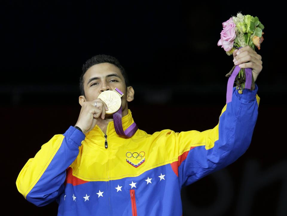Venezuela's Ruben Limardo Gascon celebrates on the victory stand after defeating Norway's Bartosz Piasecki in the gold medal match in men's individual epee fencing competition at the 2012 Summer Olympics, Wednesday, Aug. 1, 2012, in London.(AP Photo/Dmitry Lovetsky)