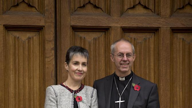 Britain's bishop of Durham Justin Welby, right, poses for photographers with his wife Caroline after a news conference following the announcement he will become the next archbishop of Canterbury at Lambeth Palace in London, Friday, Nov. 9, 2012.  The former oil executive with experience in conflict resolution has been chosen to lead a global Anglican Communion riven by sharply divided views on gay people and their place in the church. Britain's Prime Minister David Cameron announced Friday that Justin Welby, 56, a fast-rising priest with only a year's experience as a bishop, had been picked to succeed Rowan Williams as archbishop of Canterbury, spiritual leader of the world's 77 million Anglicans. (AP Photo/Matt Dunham)