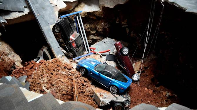 This Feb. 12, 2014 file photo shows a view of a sinkhole that opened up in the Skydome showroom at the National Corvette Museum in Bowling Green, Ky. Eight display cars were swallowed by the hole. (AP Photo/Michael Noble Jr., File)