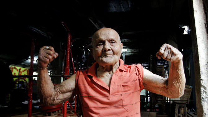 In this Friday, March 16, 2012 photo, Indian body builder Manohar Aich flexes his muscles as he poses for a photograph in a gymnasium in Kolkata, India. Aich, who is only 4 foot 11 inches (150 centimeters) tall, won the Mr. Universe title in London way back in 1952. Happiness and a life without tensions are the key to his longevity, said Aich, who turned 100 on March 17. (AP Photo/Bikas Das)