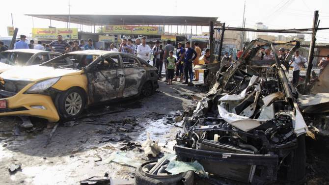 People gather at the site of a car bomb attack in the Shi'ite holy city of Karbala, southwest of Baghdad