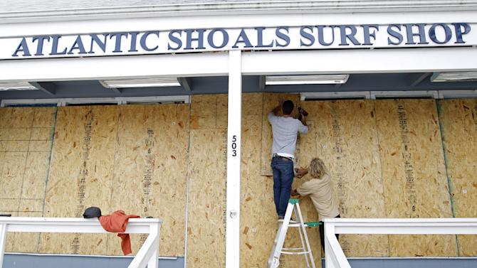Surf store workers Fletcher Birch, left, and Jay Kleman board up the windows of the store in Ocean City, Md. on Saturday, Oct. 27, 2012 as Hurricane Sandy approaches the Atlantic coast. (AP Photo/Jose Luis Magana)
