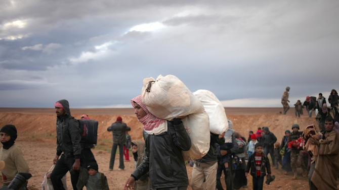 Newly-arrived Syrian refugees carry their belongings after crossing into Ruweishid, Jordan, Thursday, Dec. 5, 2013. They are part of the 1,000 Syrians to cross into Jordan Thursday, using a desert route in the east near the Iraqi border. The Jordanian army said the refugees have occasionally used the route previously, but have been doing so more frequently in the past few months because it is safer being away from Syrian towns closely monitored by forces loyal to President Bashar Assad.(AP Photo/Mohammad Hannon)