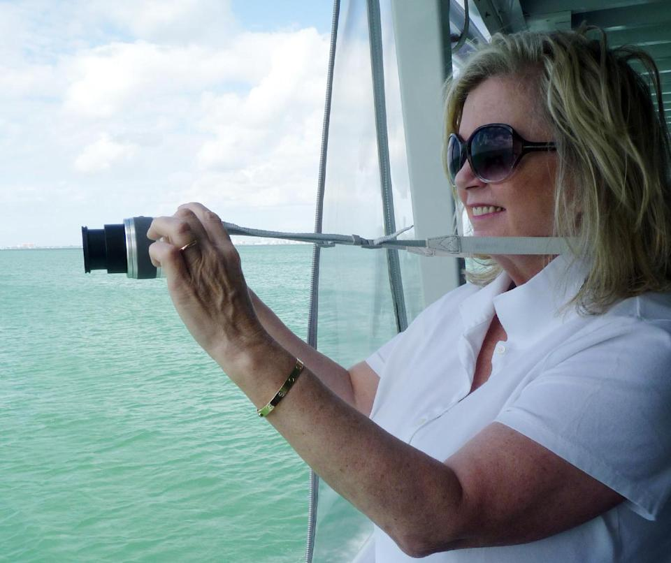 In this photo taken Sunday, Nov. 11, 2012, Karen Clark of Saratoga Springs, N.Y., takes a photo of one of the seven Stiltsville homes near Miami, Fla. The narrated tour tells the colorful story of these homes perched above the shallow waters of Biscayne Bay. (AP Photo/Suzette Laboy)