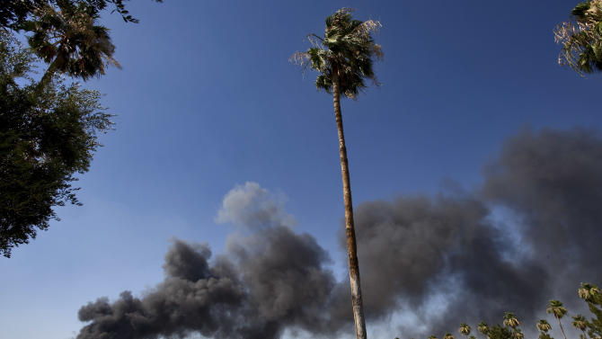 Smoke billows above a residential neighborhood from a two-alarm fire at a plumbing wholesale company near an industrial park, Monday, June 18, 2012, in Gilbert, Ariz. Flames could be seen for miles throughout the valley as firefighters battled the blaze in 110 degree heat. Mesa, Ariz Fire Capt. Mark Justus said the fire apparently started in plastic piping outside then spread to gas tanks and fiberglass. (AP Photo/Matt York)